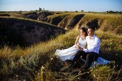 在摆在与完善的天空的日落的领域、恋人或者新婚佳偶的美好的夫妇 免版税库存照片