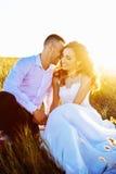 在摆在与完善的天空的日落的领域、恋人或者新婚佳偶的美好的夫妇 库存图片