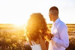 在摆在与完善的天空的日落的领域、恋人或者新婚佳偶的美好的夫妇 图库摄影