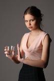在摆在与杯的桃红色上面的青少年的模型水 关闭 灰色背景 免版税图库摄影