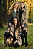 在摆在中央公园的秋天典雅的衣裳的三个美好的年轻模型 库存图片
