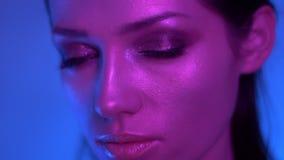 在摆在入照相机的五颜六色的紫色和蓝色霓虹灯的明亮的时装模特儿在专心地观看入它的演播室 股票视频