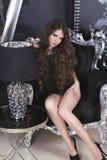 在摆在勒克斯的短的黑礼服的美好的深色的女孩模型 库存图片