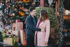 在摆在圣诞节市场上的温暖的衣裳的愉快的夫妇 免版税图库摄影