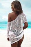 在摆在夏天海滩的透明白色女衬衫的晒日光浴的妇女模型 图库摄影