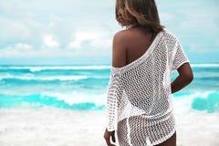 在摆在夏天海滩的透明白色女衬衫的晒日光浴的妇女模型 库存图片