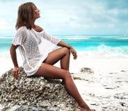 在摆在夏天海滩的透明白色女衬衫的晒日光浴的妇女模型 免版税库存图片