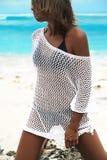 在摆在夏天海滩的透明白色女衬衫的晒日光浴的妇女模型 免版税库存照片