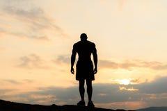 在摆在日出或日落的爱好健美者剪影的后面看法在山 显示他的英俊的大力士 免版税库存图片