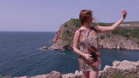在摆在海附近的礼服的女孩红色头做selfie电话 有风的日 股票视频