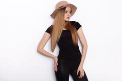 在摆在演播室的妇女黑T恤杉时髦帽子黑色被撕毁的牛仔裤的年轻美好的时装模特儿反对白色背景 图库摄影