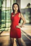 在摆在现代玻璃样式城市背景的红色礼服的美好的亚洲女孩模型 晴朗的日 免版税库存照片