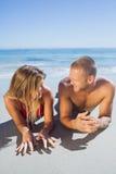 在摆在的泳装的微笑的逗人喜爱的夫妇看彼此 免版税库存照片