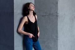 在摆在站立的放松的倾斜在墙壁的便衣的皮包骨头的年轻欧洲女性模型看远离照相机 库存图片