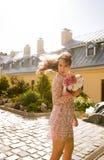 在摆在街道的桃红色鞋带礼服的美好的年轻模型  库存照片