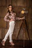 在摆在金属墙壁和葡萄酒灯附近的白色长裤的美好的深色的女孩模型 图库摄影