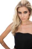 在摆在黑的礼服的华美的白肤金发的模型看照相机 图库摄影