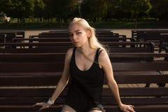 在摆在r的一条长凳的时髦的衣裳的美好的白肤金发的模型 库存照片