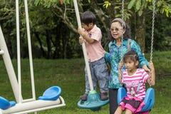 在摇摆的亚洲家庭在公园 图库摄影