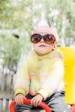 在摇摆的孩子佩带的太阳镜 免版税库存图片