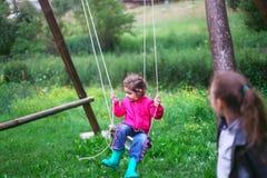 在摇摆的小女孩飞行在乡下 童年,自由, 免版税库存图片