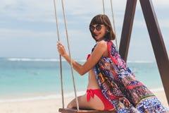在摇摆的美好的年轻女性开会在海岸 可视巴厘岛美丽的印度尼西亚海岛kuta人连续形状日落的城镇 Pandawa海滩 免版税库存图片