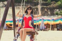 在摇摆的美好的年轻女性开会在海岸 可视巴厘岛美丽的印度尼西亚海岛kuta人连续形状日落的城镇 Pandawa海滩 免版税库存照片