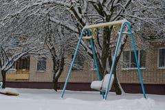 在摇摆街道,操场上的孤独的孩子,在雪下的冬天,在一个城市围场 免版税库存照片