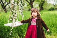 在摇摆附近的小女孩 免版税库存照片