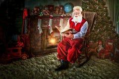 在摇椅的圣诞老人与书 免版税库存照片