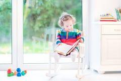 读在摇椅的逗人喜爱的小孩女孩一本书 图库摄影