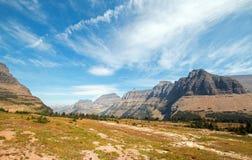 在摇石通行证的暗藏的湖供徒步旅行的小道在2017秋天火期间的卷云下在冰川国家公园在蒙大拿美国 免版税库存照片