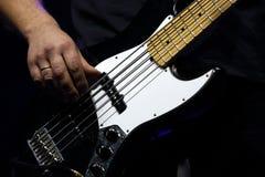 在摇滚乐音乐会期间,吉他弹奏者弹低音吉他 免版税库存图片