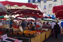 在摊位的人买的菜在新鲜市场上在一个老欧洲城市 图库摄影
