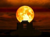 在摒弃剪影寺庙的超级纯种月亮在海 免版税库存图片