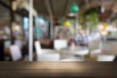 在摘要前面的空的黑暗的木桌弄脏了餐馆bokeh背景  库存照片