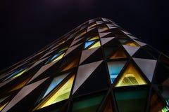 在摘要的办公室玻璃大厦在晚上 图库摄影