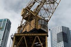 在摩天大楼之间的大起重机 免版税图库摄影
