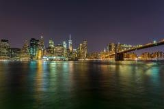 在摩天大楼的看法在从布鲁克林地平线的更低的曼哈顿在纽约在晚上 免版税库存照片
