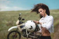 在摩托车旁边的骑自行车的人女孩 免版税图库摄影