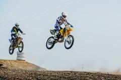 在摩托车的两个车手从山跳并且飞行 免版税库存照片