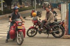 在摩托车的中国出租汽车司机 出租汽车骑自行车的人 库存照片