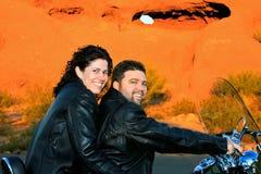 在摩托车的夫妇在红色岩石前面 库存图片