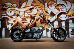 在摩托车的性感的女孩比基尼泳装 免版税库存图片