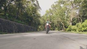 在摩托车的成人人摩托车骑士骑马在绿色树的郊区路环境美化 旅行在摩托车的老人 影视素材