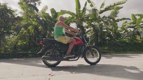 在摩托车的成熟人摩托车骑士骑马在热带棕榈树的乡下路环境美化 老人旅行 股票录像