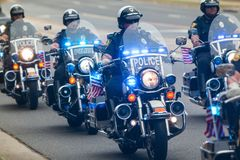 在摩托车的警察为骑自行车的人提供伴游在慈善乘驾 库存图片