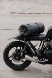 在摩托车附近的皮革背包 半在车库的黑摩托车 摩托车kaferacers 免版税图库摄影