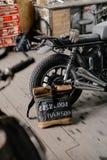 在摩托车附近的皮革背包 半在车库的黑摩托车 摩托车kaferacers 免版税库存图片