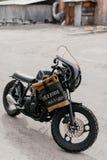 在摩托车附近的皮革背包 半在车库的黑摩托车 摩托车kaferacers 库存照片